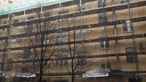 Bâtiment beige avec des rangées multiples des échafaudages de construction montés à la façade banque de vidéos