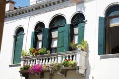 Bâtiment blanc antique avec les fenêtres en bois vertes avec dans Venezia Image libre de droits