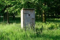 Bâtiment démodé de toilette avec la position en bois de porte extérieure parmi l'herbe avec des arbres à l'arrière-plan images libres de droits