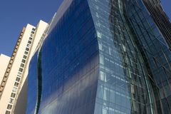 Bâtiment d'entreprise bleu incurvé moderne à côté de classique jaunâtre image stock