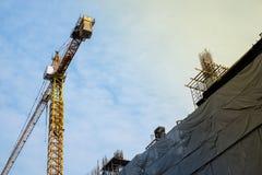 Bâtiment de chantier de construction avec les grues jaunes sur le ciel avec le nuage Images libres de droits