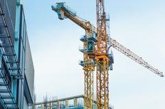 Bâtiment de chantier de construction et grue jaune photographie stock libre de droits