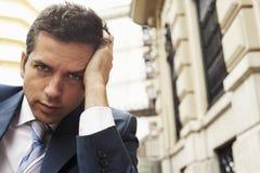 Bâtiment de With Headache Against d'homme d'affaires image stock