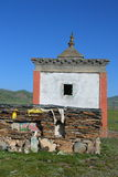 Bâtiment de roue de prière et pile des feuilles en pierre avec des incantations sur le plateau tibétain Images libres de droits