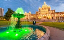 Bâtiment de Victoria Parliament entouré par le jardin la nuit, Britannique photographie stock libre de droits