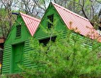 Bâtiment en bois vert caché derrière des arbres image libre de droits