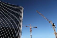 Bâtiment en construction de site avec le gratte-ciel de grue et en verre Photos libres de droits