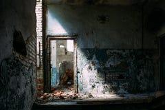 Bâtiment intérieur industriel abandonné, porte dans la lumière lumineuse et ombre Photos libres de droits