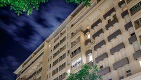 Bâtiment la nuit avec les nuages mobiles Images libres de droits