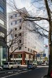 Bâtiment moderne commercial avec les arbres sans feuilles dans le premier plan et l'autobus mobile sur la route à Sapporo au Hokk Photo libre de droits