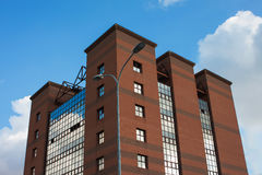 Bâtiment moderne de brique et de verre sur un fond de ciel bleu avec des nuages Photographie stock libre de droits