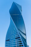 Bâtiment moderne de gratte-ciel de ville de conception (tordue) peu commune sur le ciel bleu de coucher du soleil Image libre de droits