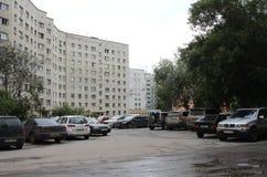 Bâtiment résidentiel à plusiers étages de Sorge de yard de rue en pierre nuageuse de Novosibirsk encombré avec les voitures sales images libres de droits