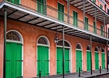 Bâtiment rose avec les portes vertes et le quartier français de volets Images stock