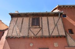 Bâtiment rougeâtre gentil de style médiéval avec sa fenêtre en bois fermée dans une des rues étroites de Ségovie Architecture His photos stock