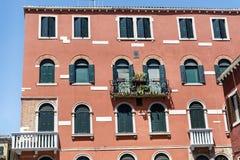 Bâtiment rouge typique avec les fenêtres antiques à Venise Photo stock