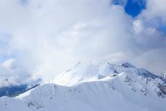 Bâtiment sur le dessus de l'arête neigeuse de montagne à la lumière du soleil et aux nuages Photographie stock