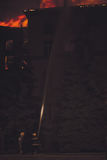 Bâtiment sur le feu la nuit Images stock