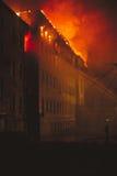 Bâtiment sur le feu la nuit Photos stock
