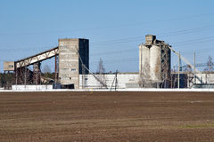 Bâtiments agricoles sur le fond d'un champ labouré et d'un ciel bleu Photo stock