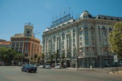 Bâtiments avec l'hôtel sur la rue passante avec des personnes et des voitures à Madrid photo stock