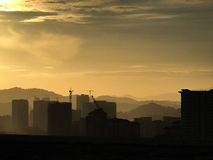 Bâtiments de sillohuette de montagnes au fond Photos libres de droits