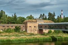 Bâtiments du fort prussien historique sur la rivière de Warta et une passerelle moderne images stock