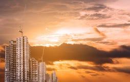 Bâtiments en construction avec la grue à tour dans le coucher du soleil, ville se développante Images libres de droits