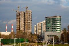 Bâtiments en construction et trois grues à coté Photo stock