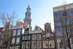 Bâtiments tordus et colorés d'héritage, situés le long du canal de Bloemgracht, avec le clocktower d'église de Westerkerk dans le photo stock