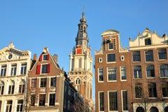 Bâtiments tordus et colorés d'héritage, situés le long du canal de Kloveniersburgwal, avec le clocktower d'église de Zuiderkerk d photographie stock