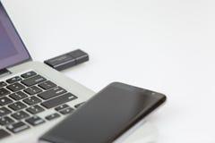 Bâton d'Usb branché et smartphone sur l'ordinateur portable Photographie stock