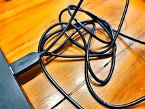 Bâton de câble de corde de noir de connecteur d'USB avec l'ordinateur portable sur la table en bois brune photographie stock