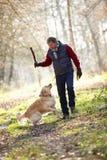 Bâton de lancement d'homme pour le chien sur la promenade image stock