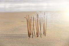 Bâton et fumée d'encens du burning d'encens Bâton d'encens brûlant sur la plage, dans la perspective de la mer Beau photos stock