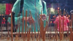 Bâtons brûlants d'encens de femme dans le temple bouddhiste banque de vidéos