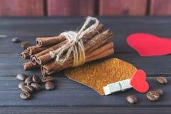 Bâtons de cannelle avec les grains de café rôtis décorés des coeurs et de la goupille de tissu sur des planches StValentine en bo Image libre de droits
