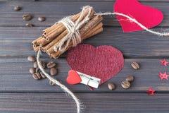 Bâtons de cannelle avec les grains de café rôtis décorés des coeurs et de la goupille de tissu sur des planches StValentine en bo Photos libres de droits