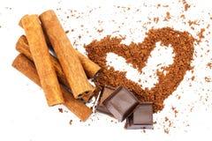 Bâtons de cannelle, cubes en chocolat et poudre de cacao dans la forme du coeur, d'isolement sur le fond blanc Image libre de droits