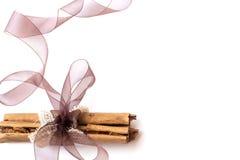 Bâtons de cannelle enveloppés en toile de jute et organza sur un fond blanc Photos stock