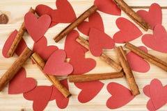 Bâtons de cannelle et coeurs rouges sur un fond en bois Images stock