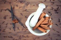 Bâtons de cannelle parfumés en mortier et épices sur le conseil rustique Image stock