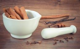 Bâtons de cannelle parfumés en mortier et épices sur le conseil rustique Photos stock