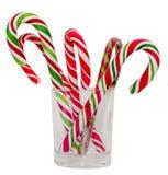 Bâtons de sucrerie et lucettes colorés de Noël dans un verre transparent, fond d'isolement et blanc Photo stock