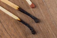 Bâtons en bois brûlés de matchs sur un fond en bois de table photo stock