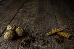 Bâtons et poivre de cannelle d'anis de noix sur un fond en bois Images libres de droits