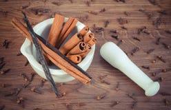 Bâtons parfumés de cannelle et de vanille en mortier sur le conseil rustique Photographie stock libre de droits