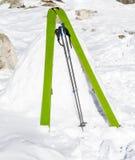 Bâtons verts de ski dans la neige Image stock