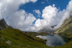 Balea lake and Balea Hotel in spring time with clouds Royalty Free Stock Photography