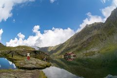 Balea lake and Balea Hotel in spring time with clouds Royalty Free Stock Photo